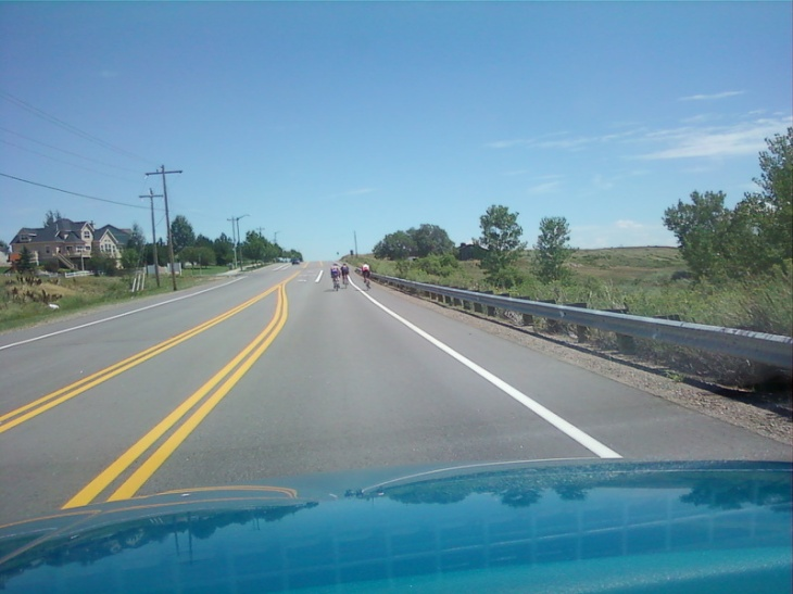 Photo taken from my teal pickup of bicyclists riding their bikes in the auto lane instead of the designated bike lane
