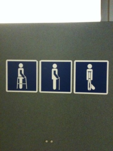 Photo of a sign in a restroom where one of the figures on the sign appears to have a tail