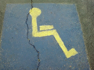 Photo of a handicap parking space where they forgot to paint a wheelchair under the person