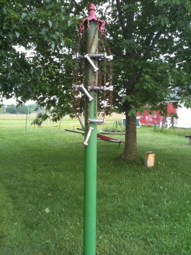 Photo of a pole that resembles a tetherball pole, but with metal chains and bars instead of a tetherball