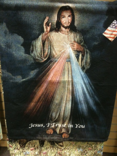 "A blanket with a photo of Jesus with red and blue beams of light shining outward from his heart that says ""Jesus, I Trust in You"" at the bottom"