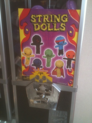 Photo of a quarter machine at Steak 'N Shake that dispenses string dolls that look like voodoo dolls
