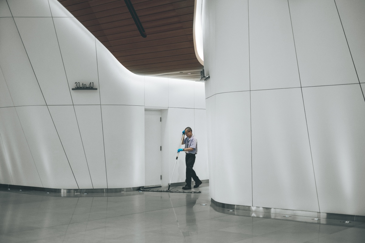 Janitor sweeping floor in modern office building